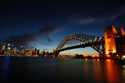 Sydney skyline and harbour bridge at dusk.